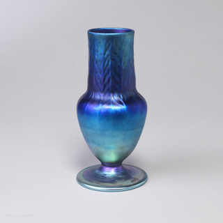 Blue-green iridescent vase, with wide foot, mounted with amphora-shaped body with distended oversized neck. Neck in-stamped with vertical chevron pattern of simple leaf forms that disappear into base.
