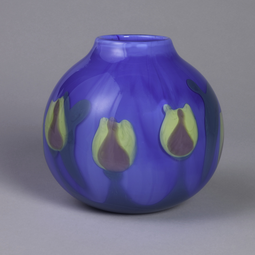 Globular formed vase in light blue with yellow tulip-like flowers.
