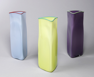 Tall triangular vase, mold blown, with rounded angles and irregular surfaces. Flat base. Body of translucent lavender, cased with clear glass. Applied lip thread of pale green opaque glass.