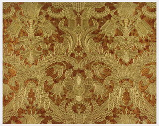 Renaissance pattern with heavy, symmetrical flower and fern motifs embossed in gold on watered salmon, gold ground.