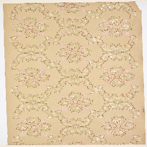 On tan ground, treillage composed of fluffy scrolls in white, green, and pink, containing scrolled rounded crosses.