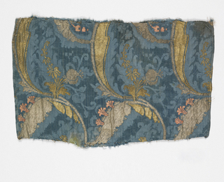 Woven silk with vertical columns of elaborately curving scrolls in gold and silver metallic brocade with pink flowers on a blue damask background.