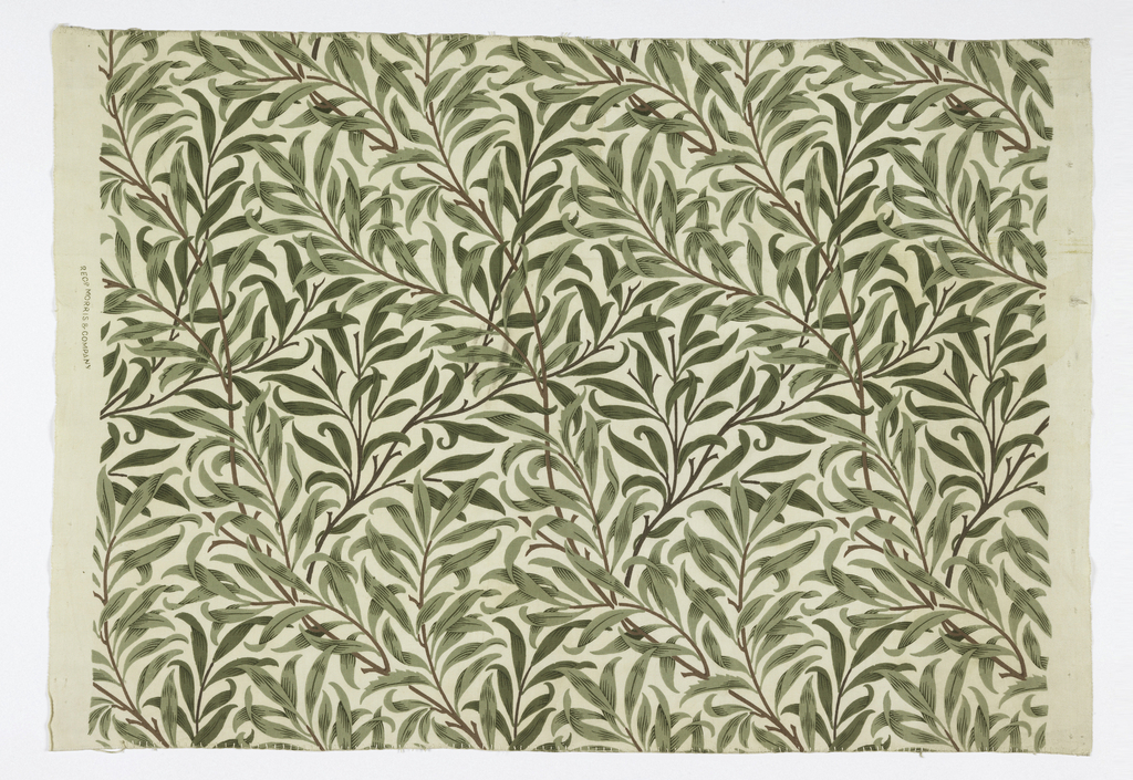 Printed cotton with an all-over design of curving willow branches and leaves, in brown and various shades of green on an off-white ground.