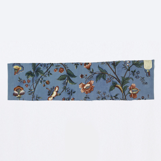 Long flowering stalks in greens, reds, yellow and white with red and blue outlines, widely spaced on a deep blue ground. In the style of 18th century painted silks. Wide plain blue selvedge.