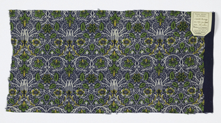 Symmetrical small-scale design of arabesques and ogees formed by twining plant stems, flowers and leaves, in white, yellow, and green on a dark blue ground with a tiny all-over floral resist pattern.