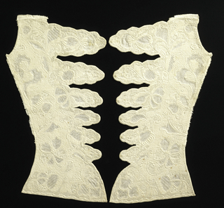 Two shaped bodice fronts with six extended tabs for lacing, in white linen with white embroidery, open-work embroidery and trapunto (stuffed quilting) in a pattern of scrolling flowers and leaves.