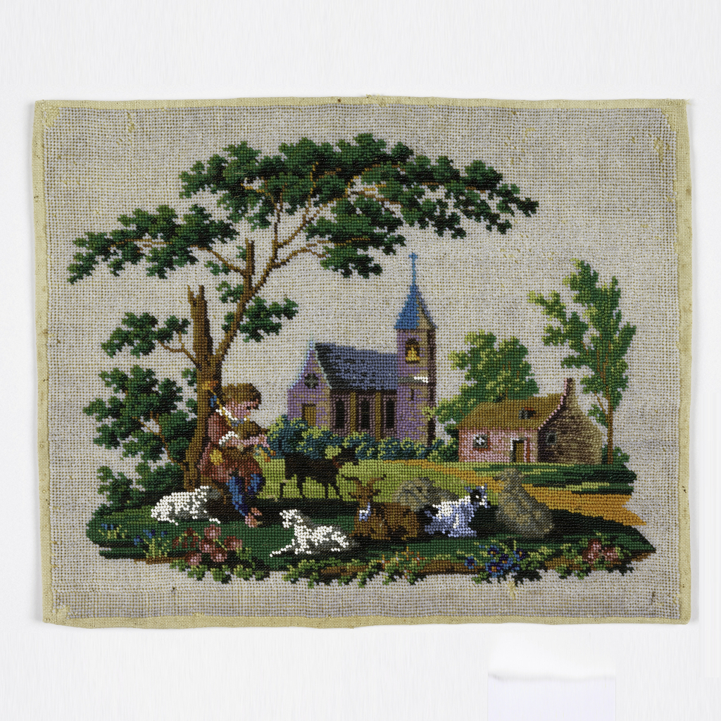 Panel of linen embroidered with colored glass beads to create a landscape scene with a church and a house, and a boy playing pipes under a large tree surrounded by sheep and goats.