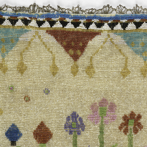 Linen panel embroidered with colored glass beads showing vase with flowers between two trees. Geoometric bands beneath the vase and triangular points in blue and red above. Thin blue border and trimmed in silver bobbin lace.
