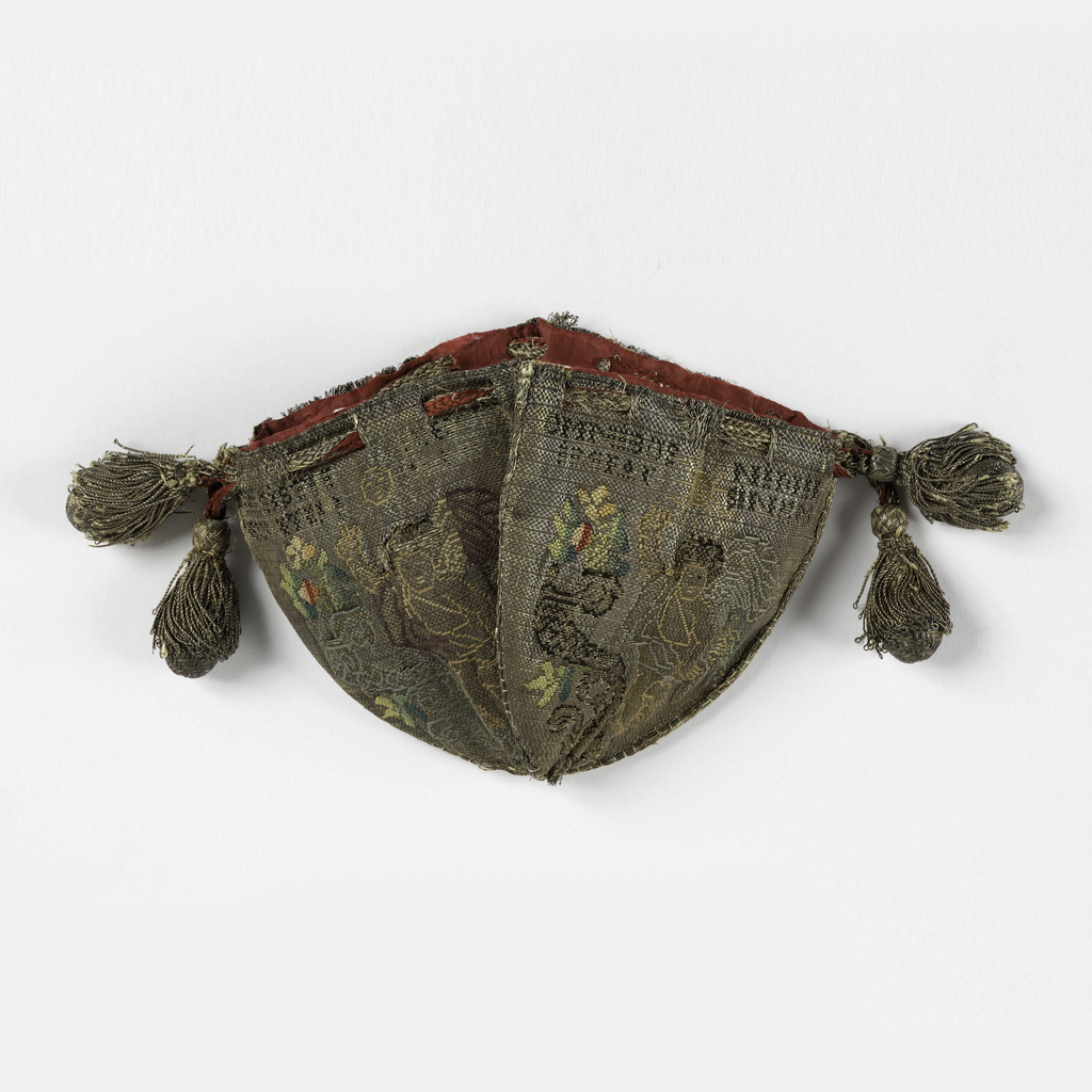 Small silk bag composed of four shield-shaped panels in cloth of silver brocaded in silk. A winged figure points to an inscription (indecipherable); a cornucopia of flowers; a sunburst. Panels joined by narrow gold braid, with draw cords of braided gold with tassels.