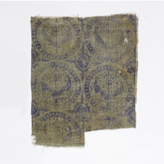 Fragment of printed linen with a repeating design of closely set roundels containing a pair of addorsed regardant birds perched in the branches of a central tree-of-life, enclosed by a broad plain band with crescent hatching. Simplified rosette in the interstices with four fleur-de-lys forms extending from it. Printed in violet-blue on an undyed linen ground.