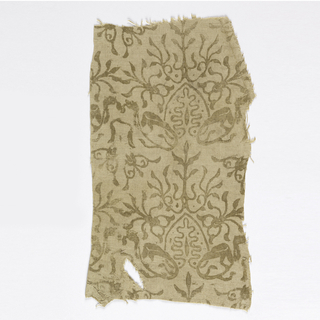 Fragment of printed linen with twining lizards forming a leaf-like form, which is surrounded by vine-like forms. In gold on an undyed ground.