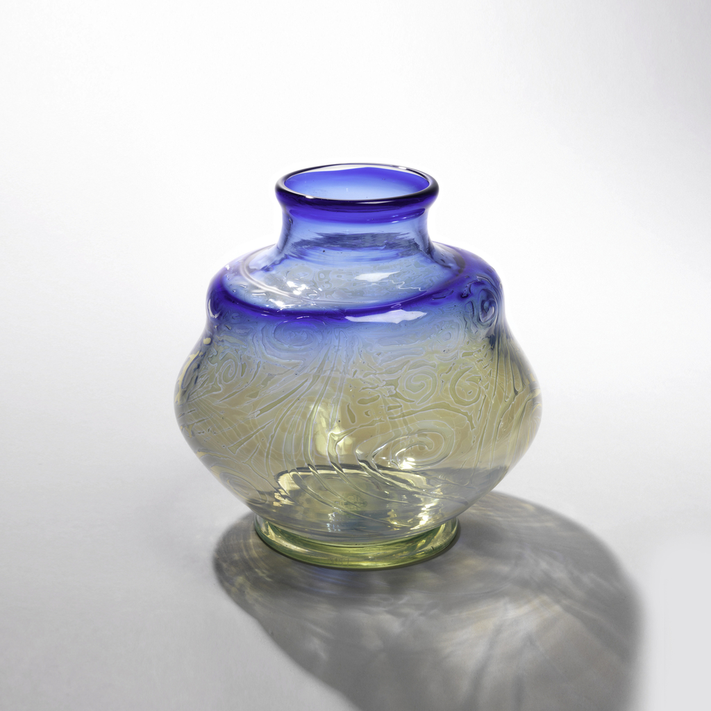 Transparent blue glass with bulging midriff; stepped shoulder; medium neck, flaring lip; low, broad foot. Deep blue lip and shoulder blending into pale blue neck, upper shoulder and body, the latter marbled with iridescent mauve-pink.