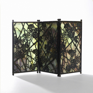 "Three vertically rectangular panels of marbleized glass, each panel framed with narrow copper edging oxidized to green and orange-red tones with two small ball feet at each end. The panels are hinged together by means of wire at juncture of feet and screen. Cut out copper overlay.  Glass marbleized in tones of lavender, blue and green overlaid with cut out copper in ""Grapevine"" pattern."