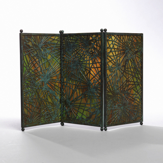 "Three vertically rectangular panels of marbleized glass, each panel framed with narrow copper edging oxidized to green and orange-red tones with two small ball feet at each end. The panels are hinged together by means of wire at juncture of feet and screen. Cut out copper overlay.  Glass marbleized in tones of red, green and amber with cut out overlay in ""Spider web"" pattern."