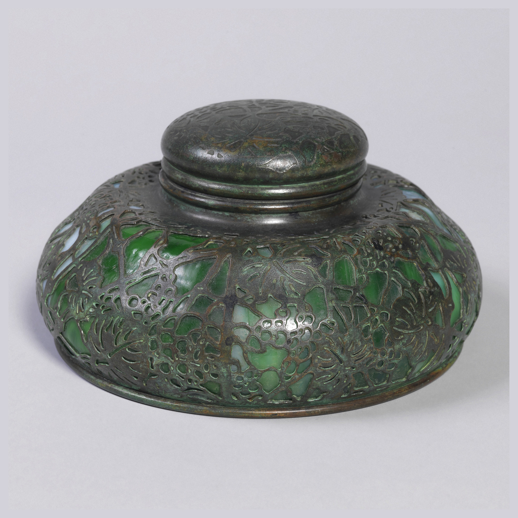 One piece of a six-piece desk set. Round ink well with lid decorated favrille glass in a grapevine pattern.