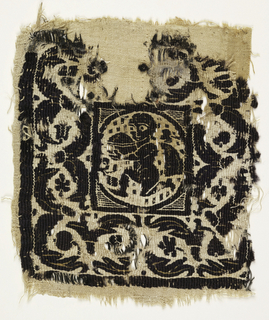 Tapestry woven square with a deep border surrounding a square field, which contains a medallion with a figure moving to the left holding a circular object, cape fluttering. Soumak defines forms and borders. Hatching in spandrels. Wide border of acanthus leaves and flowers.