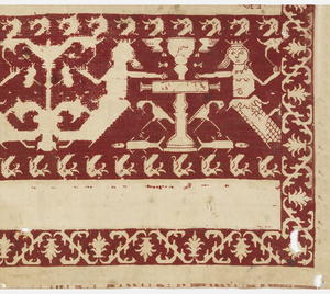 End of a table cover or towel of off-white linen embroidered in red silk with a symmetrical arrangement of mermaids and fountains. Red background is embroidered, with figures reserved in plain cloth.