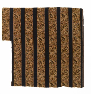 Dark brown vertical stripes alternate with stripes showing a continuous interlocking repeat of geometric designs in dark brown, tan and green on a tan satin ground.