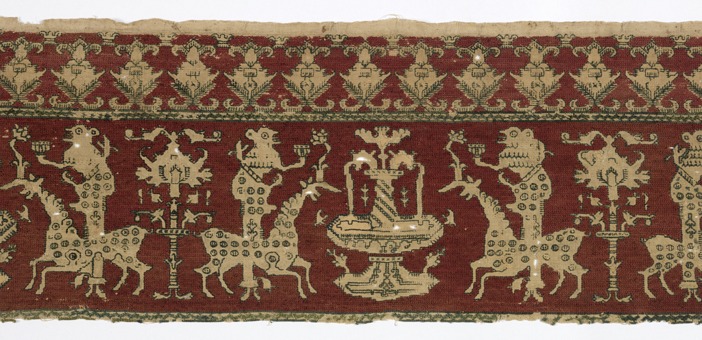 Natural color linen worked in red silk with the design reserved in the linen outlined in green silk. Details of decoration in green silk. Main design consists of a fountain flanked by grotesque figures with animal-like heads and holding a cup. Standing behind a strange four-footed beast (stag?) whose horns sprout into a flower. Above is a border of highly stylized plant forms. Piece appears to be a part of a larger embroidery as the guard border below is cut. Stitches outline in green silk closely laid chain stitch for red of background.