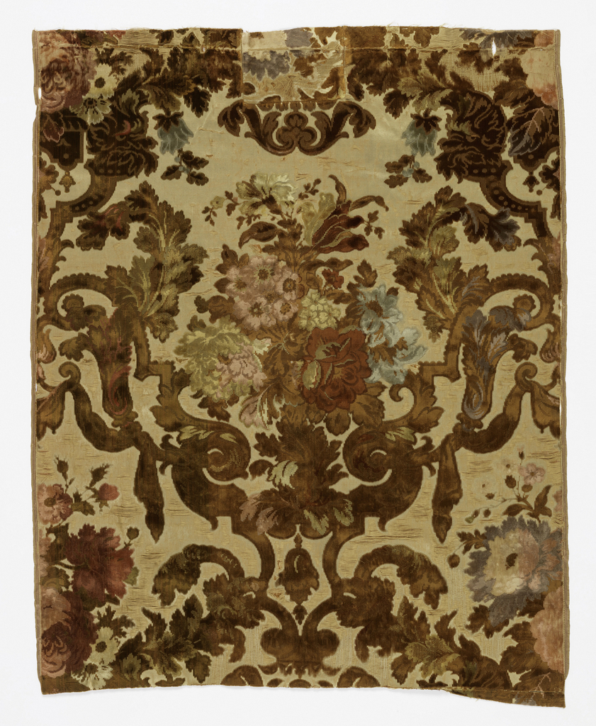 Six fragments of velvet with an ivory satin ground and cut and uncut pile in shades of brown, green, rose and red. Large scale symmetrical arrangement with a floral bouquet framed by foliage, drapery and scrolls.