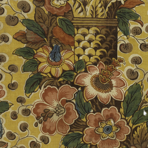 Straight repeat of a garland of polychrome flowers twisting around stacked Corinthian-style columns. Small-scale vines with brown leaves fill the yellow ground between the columns. Green color is made by printing blue over yellow.