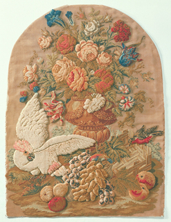 Panel from a firescreen with embroidery in raised Berlin-work.  A large urn with flowers and fruits worked in many colors, with a small red-breasted bird to the right and a large white cockatoo on the left.