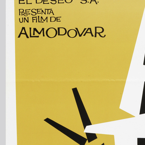 "A white background is divided in four by irregular yellow, red, magenta, and blue rectangular shapes. At the center is a triangular burst of black and white text ""A / TA / ME!"" flanked by schematic black arms, all interlaced with a jagged red ribbon.  At upper left is the inscription: ""EL DESEO S.A. / PRESENTA / UN FILM DE / ALMODOVAR"". At bottom, run the credits: ""VICTORIA ABRIL - ANTONIO BANDERAS - LOLES LEON"", continuing to the end of the page in increasingly smaller type."
