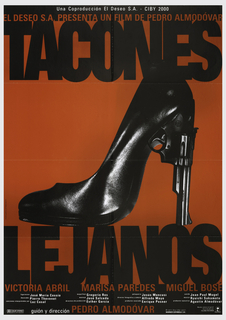 "On red background, a photograph of a polished black high-heeled shoe, the heel in the shape of a handgun, and framed by the inscription ""TACONES"" at top, and 'LEJANOS"" at bottom. At the very top is written: ""EL DESEO S.A. PRESENTA UN FILM DE PEDRO ALMODOVAR"", and at bottom are the credits: ""VICTORIA ABRIL  MARISA PAREDES  MIGUEL BOSE"" followed by further credits in smaller type."