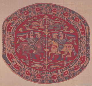 "Tapestry medallion of very fine weave with blue and tan figures on a red ground. Two confronted horsemen flank a tree; they wear a green and blue tunic, respectively, and carry swords and shields rimmed with pearl bands and their cloaks stream out behind them. Above the horsemen, a pair of horizontal branches terminating in heart-shaped leaves support a pair of confronted animals, heads reversed. A human head in the field under each horseman. The inner border contains vegetal motifs, including heart-shaped flowers and trefoils. Inner and outer degraded ""pearl"" borders."