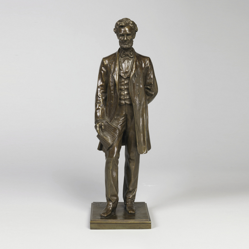 """Figure of Abraham Lincoln standing upright holding a scroll of paper with """"A LINCOLN"""" at the end of the indecipherable writing."""
