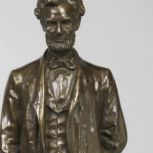 "Figure of Abraham Lincoln standing upright holding a scroll of paper with ""A LINCOLN"" at the end of the indecipherable writing."