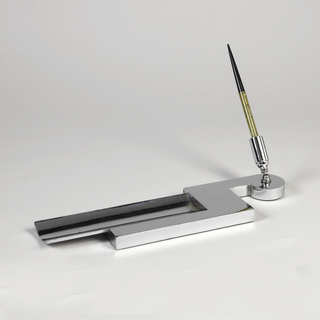 Pen tray, flat chrome-plated in elongated abstracted shape. One end rounded, center rectangular, and other end tray with curved base.