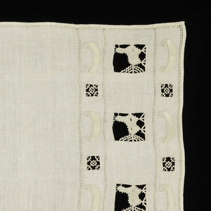 Table scarf with borders at each end of cutwork birds and wheels, embroidered canoes.