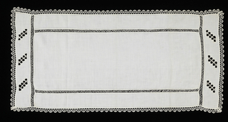 Cover with bobbin lace insertion and edging. At each end, there are three cutwork rectangles with embroidery in the design of a strawberry vine.