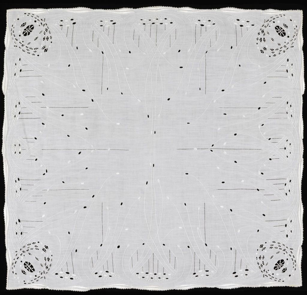 Small table cover of white linen embroidered in white linen with details in cutwork. Design of slender elongated stems rising and curving up from the border. Cutwork medallion in the corner.