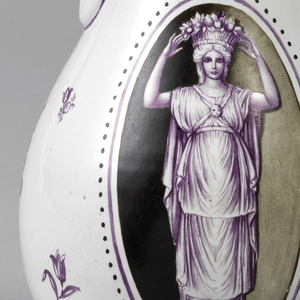 Pear form body decorated in manganese palette over white glaze with sprigs of flowers. C-scroll handle with back scroll terminal.  On the side, a female classical caryatid figure with basket of fruit on her head in an oval reserve.  The lid decorated in manganese with scrolls and dots.