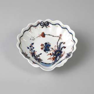 Shell form, decorated in Chinese style with carnations, in red and blue with gilt highlights, on a blue-grey glaze.