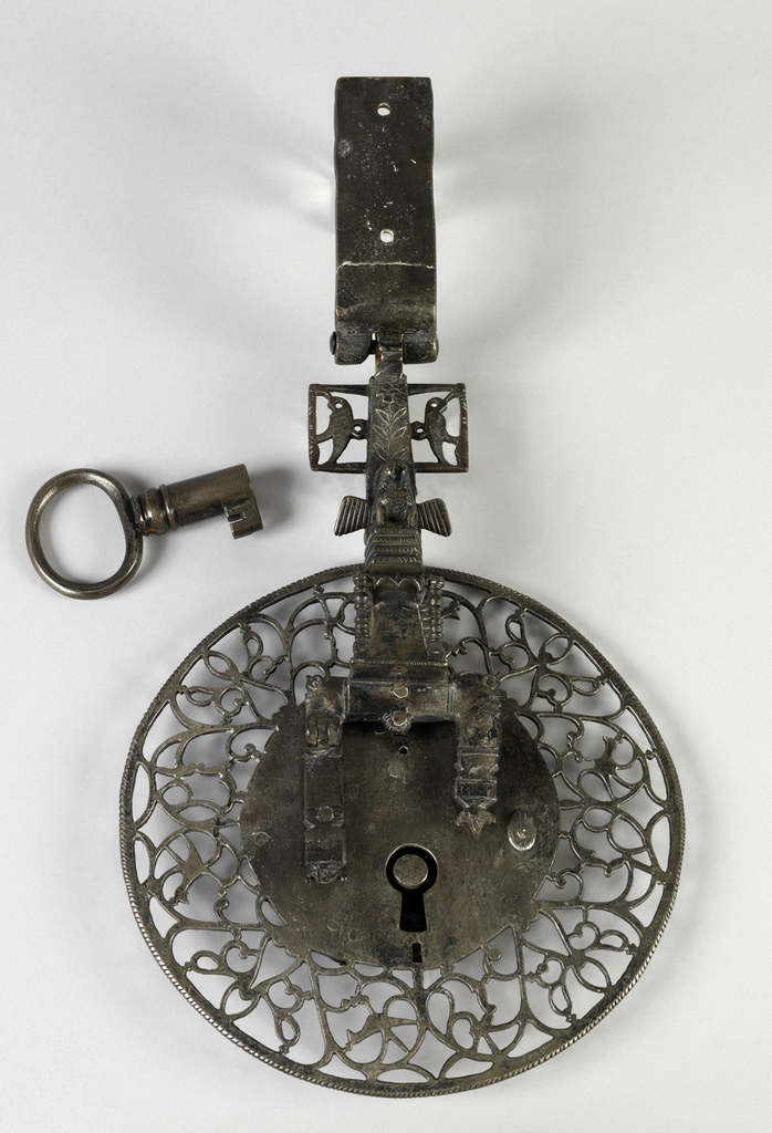 Lock in circular form, decorated with pierced vine and foliage pattern around keyhole; hasp attached with bird decoration, and short key with large loop.