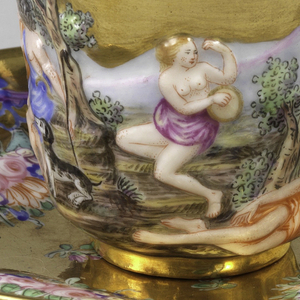 Curved flaring cup, with twisted stem handle, ending in leaves. Slightly curved saucer. On cup, relief decoration of mythological scenes (Judgement of Paris, Mercury, Neptune), enhanced with polychrome painting. Upper part of cup and inside gilded. Saucer gilded with polychrome relief festoons and cartouches.