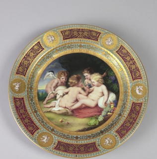 """(a: plate): On pale green marli six oblong fields of wine red, all factory decorated with raised gold arabesques, and six gold medallions with grisaille genii. In center, polychrome copy of Rubens' """"Children Playing"""": four small children, one of them winged, playing with a lamp in landscape.  (b: stand): Stand scrolled and twisted flat brass."""