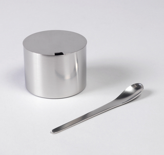 Stainless steel cylindrical vessel and spoon; with flat base and flat cover. Cover has small square-shaped opening for spoon; spoon is smooth with slightly curved bowl.