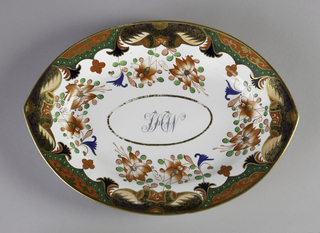 "Almond-shaped platter decorated near border with gilt, blue, red, and green flowers and abstract mounds. In well, an oval with overlapping initials: ""LHW"" (?)."