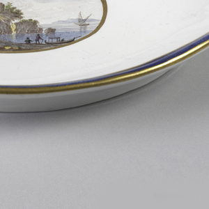 Assymetrical ovoid dish with scalloped rim, scrolled at left and right; rim decorated with wide blue band between thin gilt lines; in center, oval medallion with gilt border, showing landscape with bridge extending into body of water with two boats and two figures.