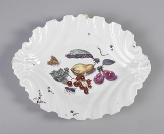 Dish with scalloped edges in ovoid; at center, fruit on stems with leaves and insects.