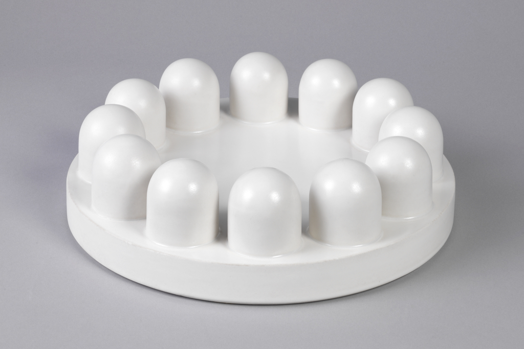 Circular dish with twelve upright rounded protrusions along rim.