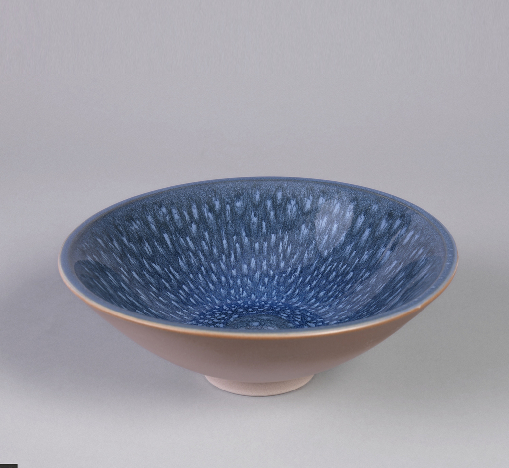 Circular bowl tapering to short circular foot; blue speckled interior.