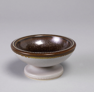 Earthenware footed bowl with brown glaze.
