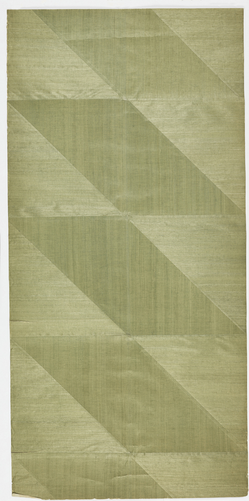 Finely textured green grasscloth cut into triangles and parallelograms and mounted to show vertical and horizontal pattern of weave alternating. Backed with Japanese paper.