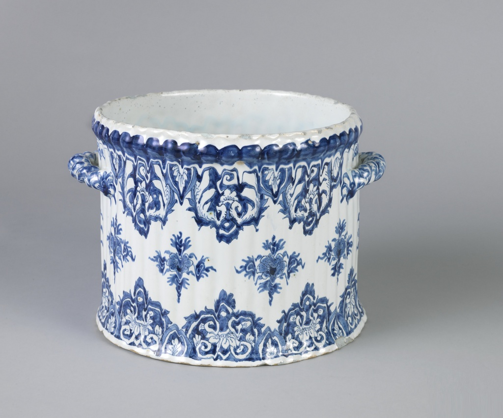 Cylindrical with slight flare at base and slight thickening at top. Ribbed sides and horizontal twisted handles. Decorated with lambrequin-like clusters of flowers and leaves at top and bottom, and square foliate medallions about center. Surface somewhat pitted.