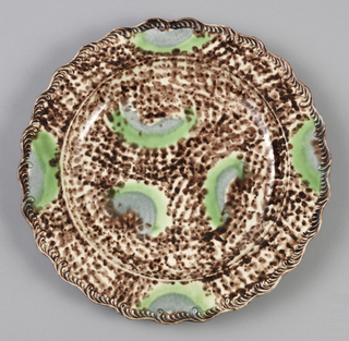 Plate with wavy border, brown speckled pattern with green and light bluish-grey biomorphic shapes.